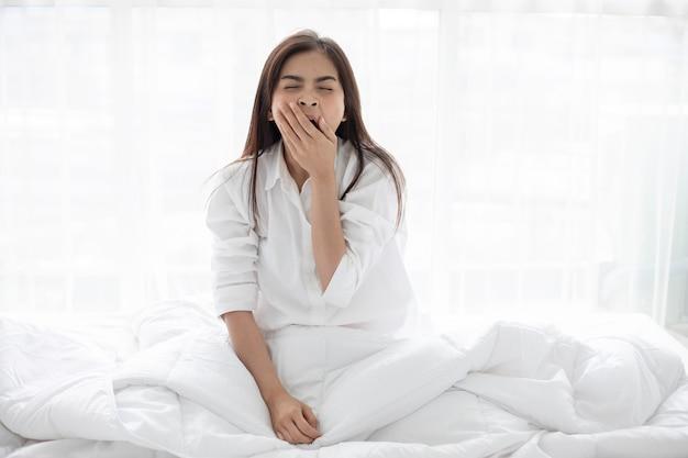 Mulher asian, mulher sorridente, sentar-se cama, e, esticar, de manhã, em, quarto, após, w