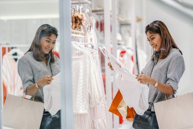 Mulher asian, olhar, e, escolha, a, roupa interior, em, loja loja, com, feliz, ação