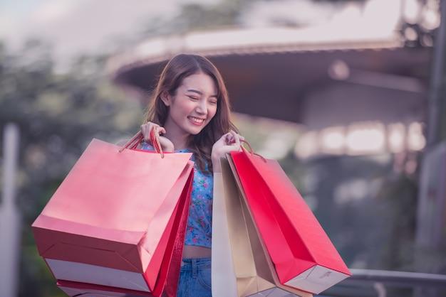 Mulher asian, segurando, bolsas para compras, e, levantado mãos cima