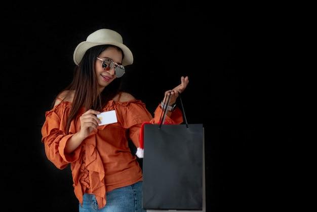 Mulher asian, segurando, cartão crédito, com, pretas, sexta feira, saco de compras, e, papai noel, chapéu