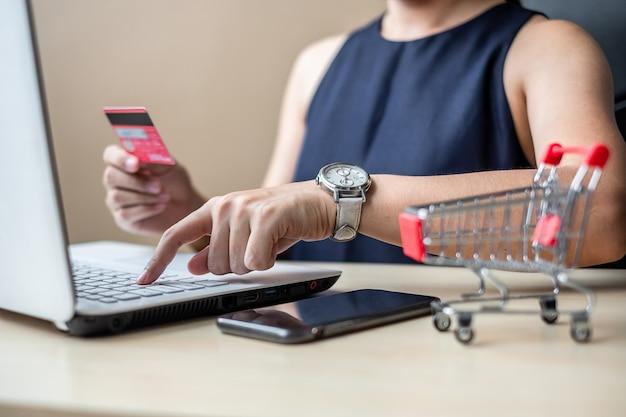Mulher asian, segurando, cartão crédito, e, usando computador portátil, para, shopping online