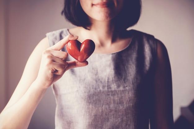 Mulher asian, segurando, coração vermelho, seguro saúde, doação, caridade, conceito