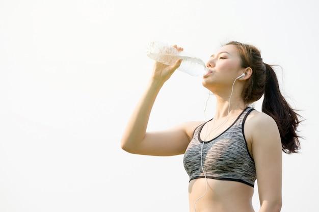 Mulher asian, segurando, garrafa água, em, mão, e, bebendo, água