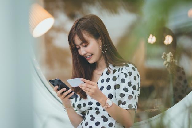 Mulher asian, segurando, um, cartão crédito, e, usando, smartphone, com, feliz