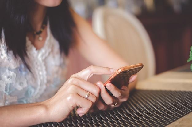 Mulher asian, sentando, em, loja café, e, usando, telefone móvel, para, verificar, mídia social