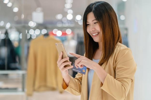 Mulher asian, usando, cartão crédito, com, telefone móvel, para, shopping online, em, loja de departamentos