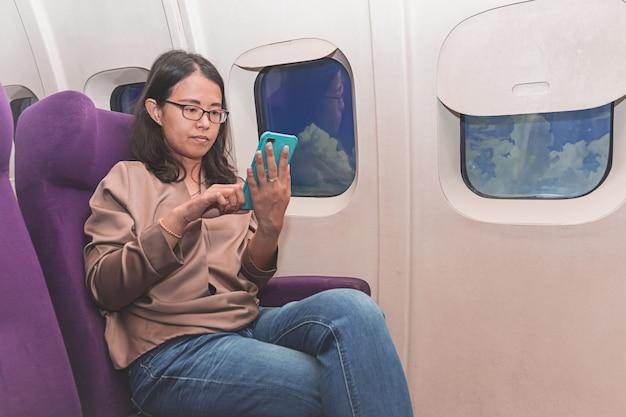 Mulher asian, uso, de, telefone móvel, dentro, avião