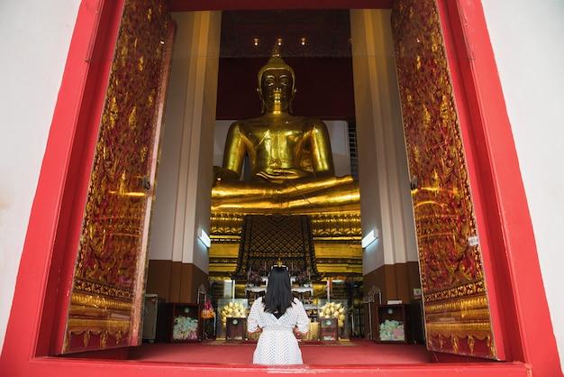 Mulher asiática a pagar respeito à estátua de buda em ayutthaya, tailândia.