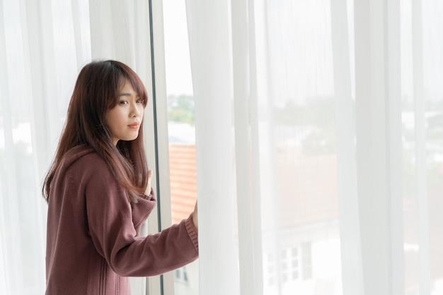 Mulher asiática abrir a cortina de manhã