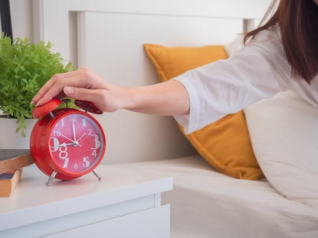 Mulher asiática acorda de manhã e desligar o despertador