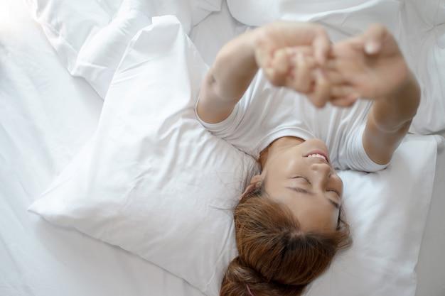 Mulher asiática acorda de manhã na cama. ela se sentiu fresca de manhã.