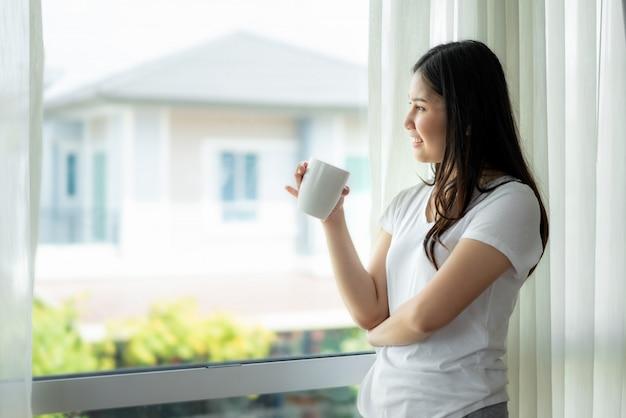 Mulher asiática acorda em sua cama totalmente descansada e abre as cortinas no peitoril da janela.