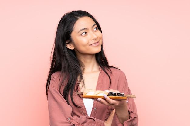 Mulher asiática adolescente comendo sushi isolado na rosa olhando para o lado