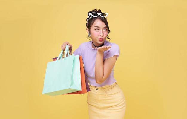 Mulher asiática adolescente feliz alegre curtindo as compras, ela está carregando sacolas de compras no centro comercial.