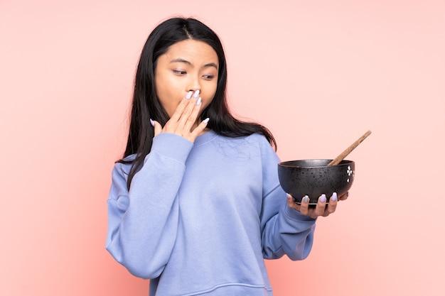 Mulher asiática adolescente isolada em um tom bege com expressão facial de surpresa e choque, segurando uma tigela de macarrão com pauzinhos