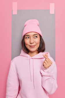 Mulher asiática adorável que faz um sinal coreano demonstra sentimentos verdadeiros e o amor mostra o gesto do coração com o dedo vestida com um moletom casual e poses de chapéu contra a parede do estúdio com uma folha de papel gessada