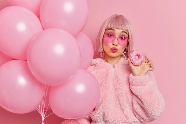 Mulher asiática adorável romântica mantém os lábios dobrados tem cabelo bob rosa vestido com casaco de pele de inverno contém deliciosa rosquinha vitrificada e balões de hélio inflados comemora aniversário na festa com amigos.