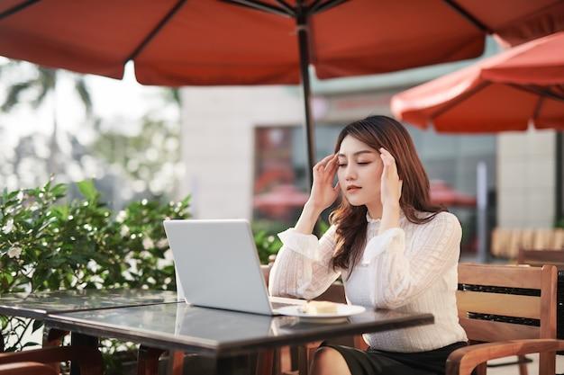 Mulher asiática adulta está trabalhando em um laptop em um café do lado de fora na rua, com dor de cabeça e enjoo, segurando as mãos na cabeça