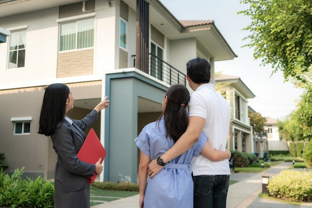 Mulher asiática agente imobiliário, mostrando um detalhe do projeto da casa em seu arquivo para o jovem casal asiático que procura e deseja comprá-lo.