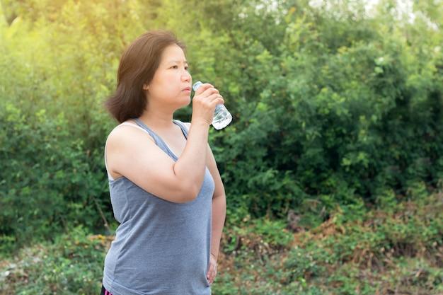 Mulher asiática água potável após o exercício de esporte, mulher de esporte segurando a garrafa de água pura