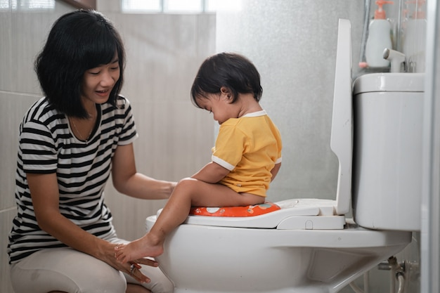 Mulher asiática ajuda a filha a sentar no vaso sanitário enquanto faz xixi no banheiro