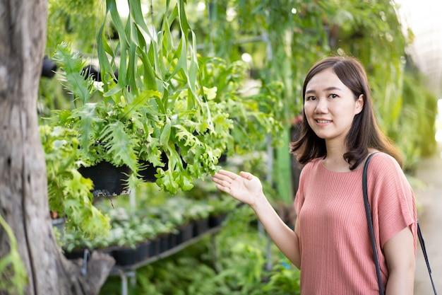 Mulher asiática alegre à procura de uma planta no mercado de jardim.