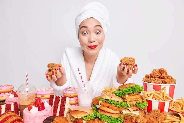 Mulher asiática alegre e surpresa olhando para a câmera cercada por fast food