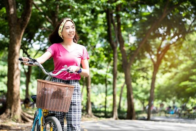 Mulher asiática alegre em um vestido esporte com cabelo curto, perto de uma bicicleta vintage e curtindo a natureza no parque público