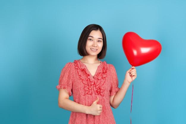Mulher asiática alegre em um vestido vermelho segura um balão vermelho voador em forma de coração e faz sinal de positivo