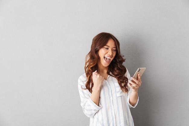 Mulher asiática alegre isolada, segurando um telefone celular, comemorando