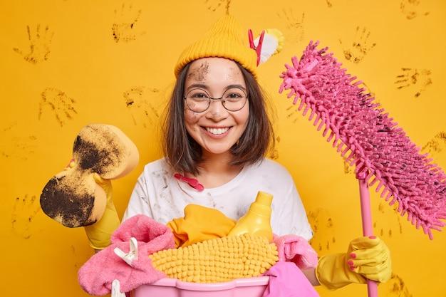 Mulher asiática alegre segura equipamento de limpeza, estando de bom humor após arrumar o quarto, usa chapéu redondo poses de óculos perto do cesto de roupa suja manchada com sujeira isolada na parede amarela