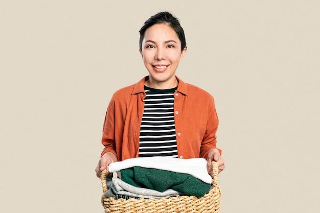 Mulher asiática alegre segurando um cesto de roupa suja