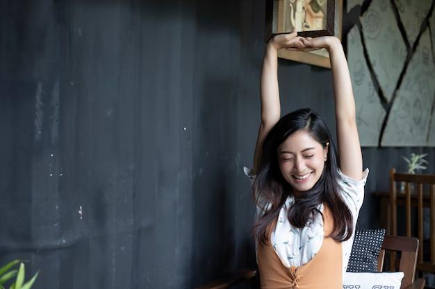 Mulher asiática, alongamento e sorrindo no escritório em casa