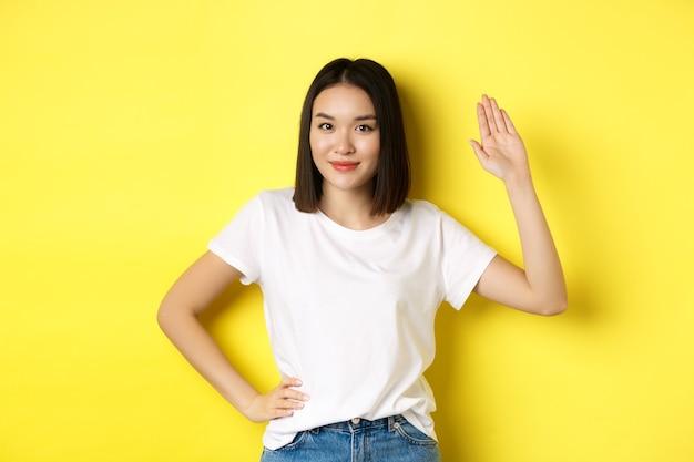 Mulher asiática amigável em t-shirt branca acenando com a mão e dizendo olá, cumprimentando você, em pé sobre fundo amarelo.
