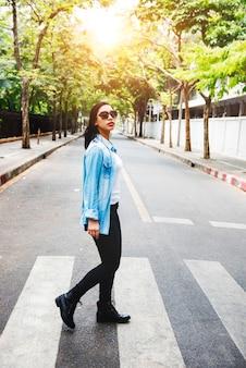 Mulher asiática andando atravessando a rua