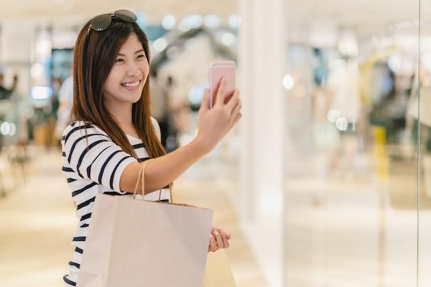 Mulher asiática andando e usando o telefone móvel inteligente para selfie com maquete de modelo