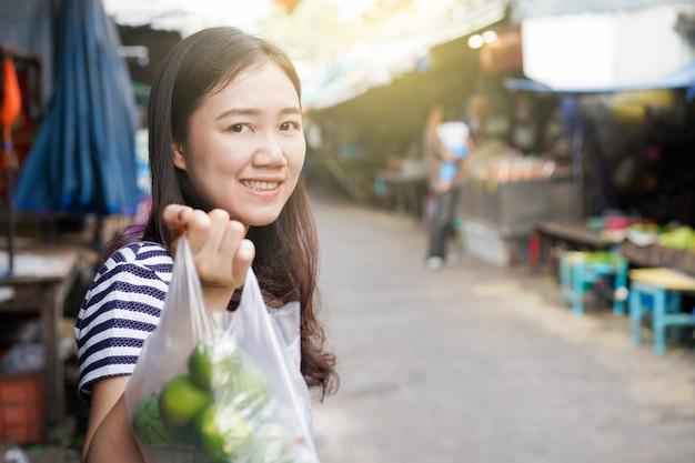 Mulher asiática andando pelo tradicional mercado de produtos frescos em bangkok, tailândia