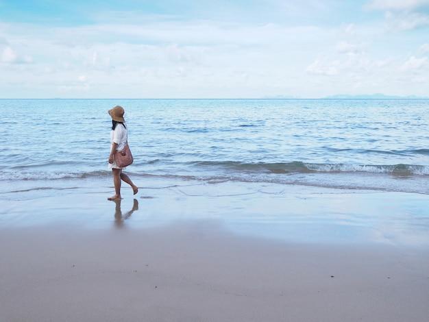 Mulher asiática andando sozinho na areia ao longo da praia de manhã.