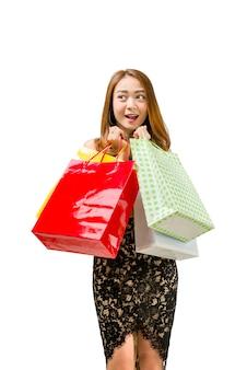 Mulher asiática animada com sacolas coloridas em pé