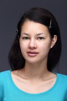 Mulher asiática antes de aplicar maquiagem camisa azul estilo de cabelo preto. sem retoque, rosto fresco com acne, pele bonita e lisa. fundo cinza com iluminação de estúdio