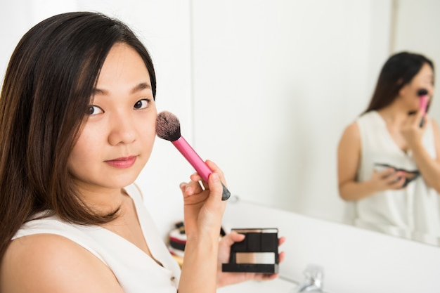 Mulher asiática, aplicar pó facial no banheiro