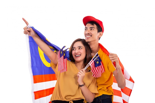 Mulher asiática, apontando enquanto segura a bandeira nacional