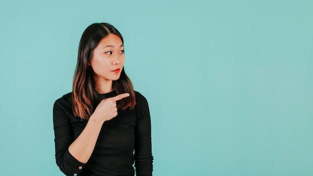 Mulher asiática apontando para a direita