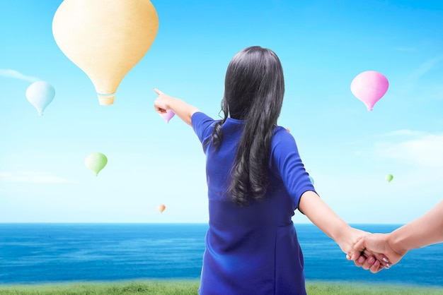 Mulher asiática apontando um balão de ar colorido voando com o fundo do céu azul