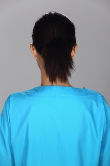Mulher asiática após a aplicação de maquiagem camisa azul estilo de cabelo preto. sem retoque, rosto fresco com acne, pele bonita e lisa. fundo cinza com iluminação de estúdio, vista traseira lateral