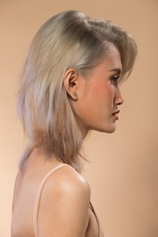 Mulher asiática após a aplicação de maquiagem estilo de cabelo cinza prateado. sem retoque, rosto novo com acne, lábios, olhos. iluminação de estúdio com fundo amarelo bege, para tratamento de terapia estética, vista traseira lateral traseira