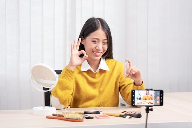 Mulher asiática apresenta produto cosmético de beleza e transmite vídeo ao vivo para rede social pela internet em casa, conceito de blogueira de beleza.