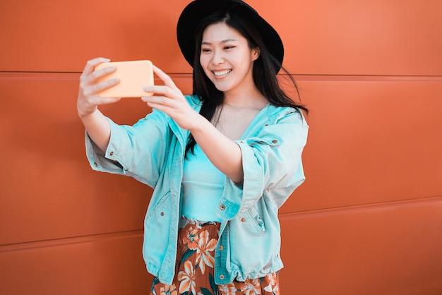 Mulher asiática asiática influenciador usando smartphone com coral. feliz menina chinesa se divertindo com as novas tendências da tecnologia