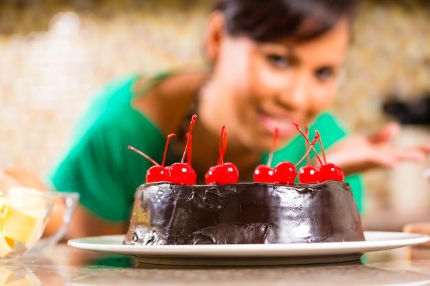Mulher asiática, assar bolo de chocolate na cozinha