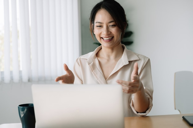 Mulher asiática assistindo webinar no laptop